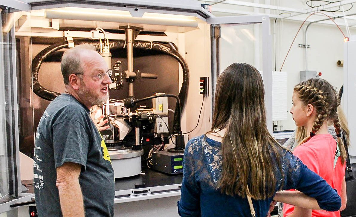 Darya Pronina of Waunakee Middle School and a friend look on as Dan Frankel, from the scientific instrument maker Bruker Corp., demonstrates a single-crystal X-ray diffractometer in the UW–Madison Chemistry Department.