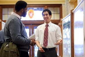 Taylor Banh, right, talks about his research project on obligatory increases in energy expenditure of MGAT2-deficient mice lead to increased food intake on low-fat diet during a poster presentation session at the Undergraduate Symposium