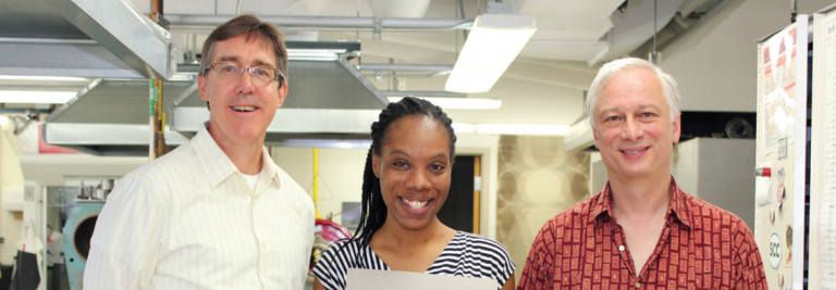 Shedeen Barnett, a scientific glassblower from Jamaica, shows off glassware she created while visiting UW-Madison to learn from glassblowers Tracy Drier and his colleague Erich Moraine.