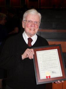 Man smiling holding certificate