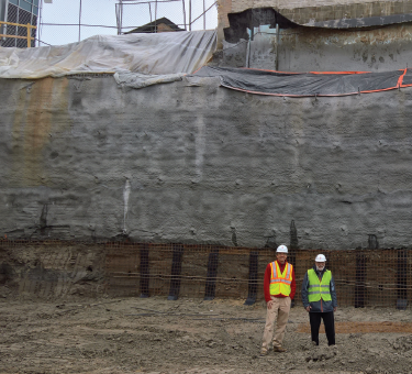 Bob McMahon and John Moore stand in the excavation area. A corner of Shain Tower is visible at the upper left.