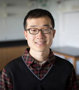 Man with dark hair, glasses, checkered button down shirt with sweater vest in a lab