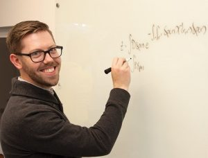 Man dressed in black, writing on glass board and smiling at the camera