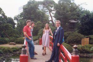 four people outside on a bridge