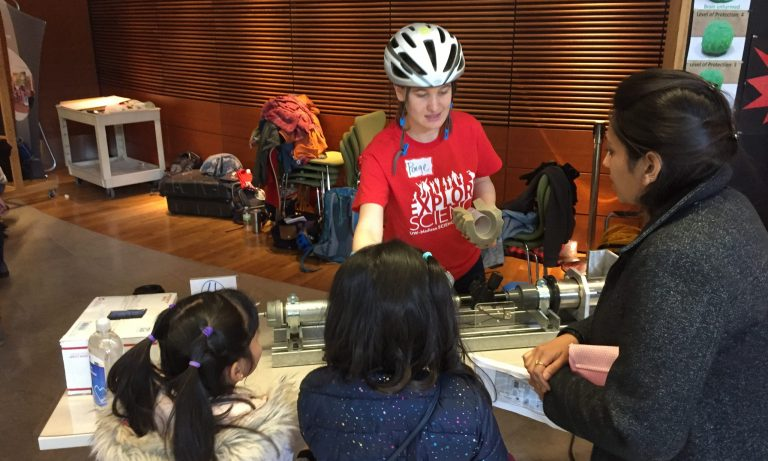 person in bike helmet speaking to children