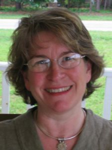 Lady with short brown hair and glasses smiling